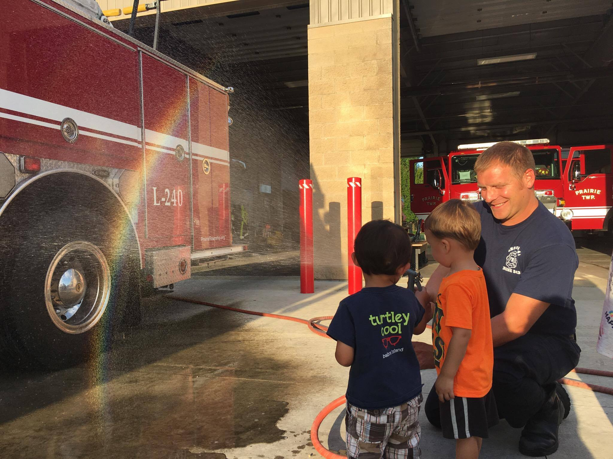 Firefighters Washing a Fire Truck with Two Kids