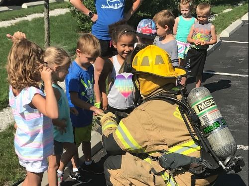 PTCC Safety Town - image of Fire Fighter in full gear talking to preschool children
